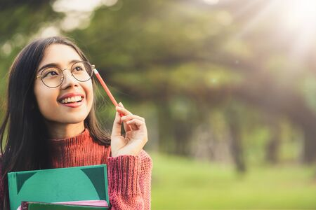 Young creative student girl thinking or planning future education while holding pencil in hand. Creativity idea and learning concept. Stockfoto