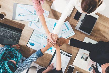 Uomini d'affari e donne d'affari che si uniscono per mano in una riunione di gruppo in un ufficio multiculturale che mostra lavoro di squadra, supporto e unità negli affari. Concetto di lavoro di diversità sul posto di lavoro e persone aziendali. Archivio Fotografico