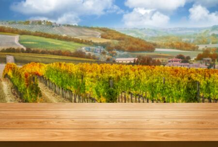 Brown wood table in autumn vineyard landscape with empty copy space on the table for product display mockup. Winery and wine tasting concept. Zdjęcie Seryjne