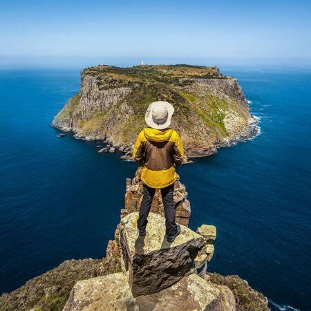 Young man trekker hiking on beautiful coast cliff of Tasman National Park in Tasman peninsula, Three Capes Track near Port Arthur in Tasmania, Australia.
