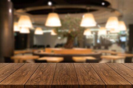 Mesa de madera en el fondo borroso de la moderna sala de restaurante o cafetería con espacio de copia vacío en la mesa para maqueta de exhibición de productos. Concepto de diseño de mostrador de restaurante interior.