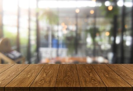 Wood table in blurry background of modern restaurant room or coffee shop with empty copy space on the table for product display mockup. Interior restaurant counter design concept. Imagens