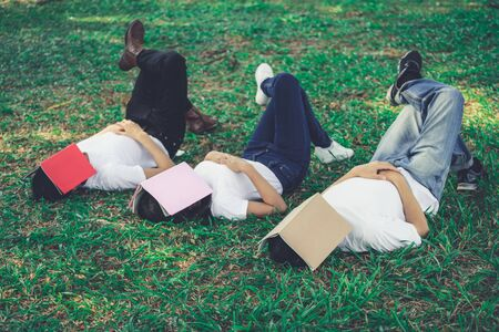 Funny students sleeping with books covering their face. Lazy and relaxation concept.