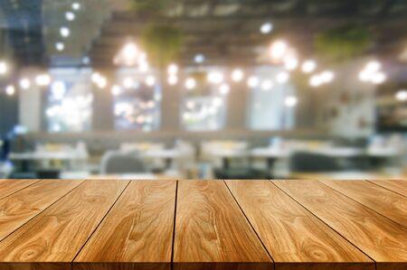 Holztisch im verschwommenen Hintergrund des modernen Restaurantraums oder Cafés mit leerem Kopienraum auf dem Tisch für Produktpräsentationsmodell. Designkonzept für die Restauranttheke im Inneren.