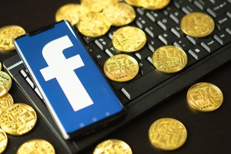 Bangkok, Thailand - July 2, 2019: Phone with Facebook logo on screen is placed keyboard. Facebook reported to utilize new cryptocurrency called Libra expected to be used on Facebook.