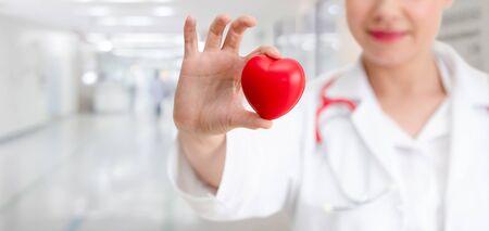 Medico che tiene un cuore rosso nell'ufficio dell'ospedale. Assistenza sanitaria medica e concetto di servizio del personale medico. Archivio Fotografico