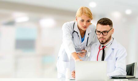 Arts die met laptopcomputer op kantoor werkt terwijl hij een gesprek heeft met een andere arts in het ziekenhuis. Medische gezondheidszorg en doktersdienst. Stockfoto