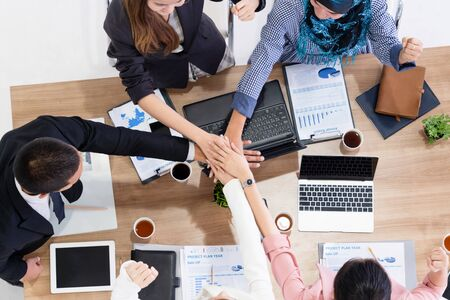 Businessmen and businesswomen joining hands in group meeting at multicultural office room showing teamwork, support and unity in business. Diversity workplace and corporate people working concept. Banco de Imagens - 128435012