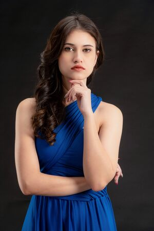 Beautiful woman fashion model in blue dress standing on dark background. Luxury advertising. Banque d'images
