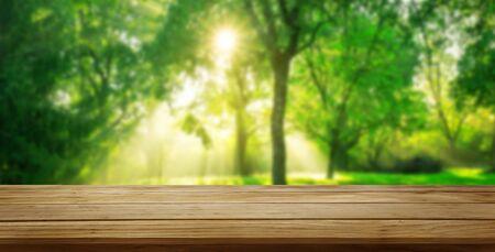 Mesa de madera marrón en verde desenfoque de fondo de naturaleza de árboles y césped en el parque con espacio de copia vacío en la mesa para maqueta de exhibición de productos. Concepto de producto natural y manantial.