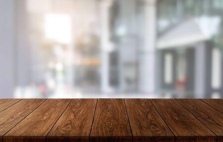 Mesa de madera en el fondo de la oficina moderna del centro de la ciudad con espacio de copia vacío en la mesa para maqueta de exhibición de productos. Interior del escritorio del área de trabajo y lugar para negocios corporativos. Foto de archivo