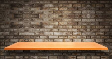 Wood table in front of rustic brick wall blur background with empty copy space on the table for product display mockup. Retro design montage presentation.