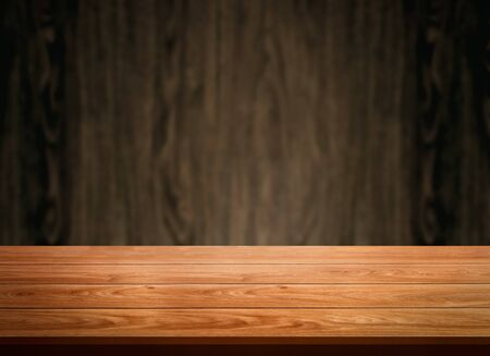Wood table in front of wood wall blur background with empty copy space on the table for product display mockup. Retro design montage presentation.