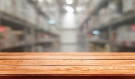 Wood table in warehouse storage blur background with empty copy space on the table for product display mockup. Hardware goods distribution and industrial logistics concept. Stok Fotoğraf