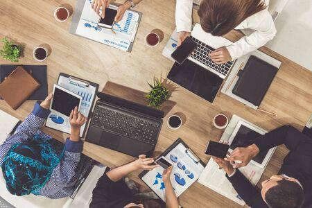 Vue de dessus de l'exécutif de l'homme d'affaires en réunion de groupe avec d'autres hommes d'affaires et femmes d'affaires dans un bureau moderne avec ordinateur portable, café et document sur table. Concept d'équipe d'entreprise de personnes.