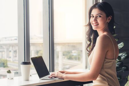 Young business woman using laptop computer while sitting at cafe table next to office windows.