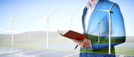 Double exposure graphic of business people working over wind turbine farm and green renewable energy worker interface. Concept of sustainability development by alternative energy. Stockfoto