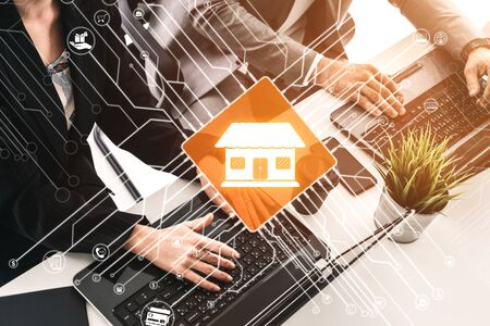 Smart Home with Computer Control Concept. Businessman and businesswoman working on laptop computers at office desk with logo of smart home. Stockfoto