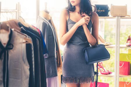 Beautiful woman shopping for clothes at retail apparel shop in the shopping mall. Modern trade lifestyle. Stock Photo