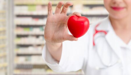 Doctor holding a red heart at hospital office. Medical health care and doctor staff service concept. Stockfoto