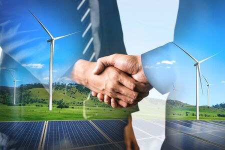 Double exposure graphic of business people handshake over wind turbine farm and green renewable energy worker interface. Concept of sustainability development by alternative energy. Stockfoto