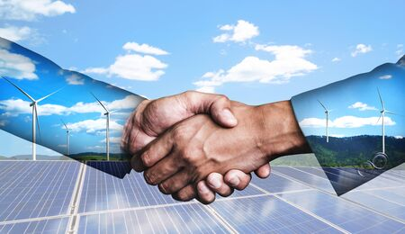 Doppelbelichtungsgrafik von Geschäftsleuten Handshake über Windturbinenpark und grüne erneuerbare Energiearbeiterschnittstelle. Konzept der Nachhaltigkeitsentwicklung durch alternative Energien. Standard-Bild