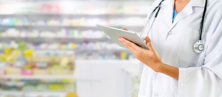 Pharmacist using tablet computer at the pharmacy. Medical healthcare and pharmaceutical staff service. 写真素材