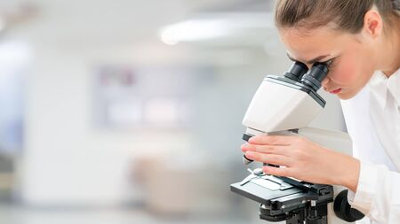 Scientist researcher using microscope in laboratory. Medical healthcare technology and pharmaceutical research and development concept. 写真素材
