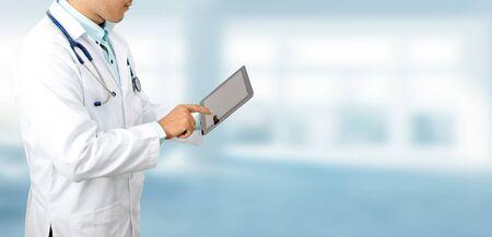 Mężczyzna lekarz przy użyciu komputera typu tablet w szpitalu. Personel naukowo-badawczy i opieka lekarska.
