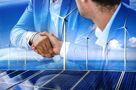 Double exposure graphic of business people handshake over wind turbine farm and green renewable energy worker interface. Concept of sustainability development by alternative energy. Banco de Imagens