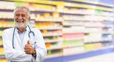 Happy senior pharmacist standing in the pharmacy. Pharmaceutical business and service. Banco de Imagens