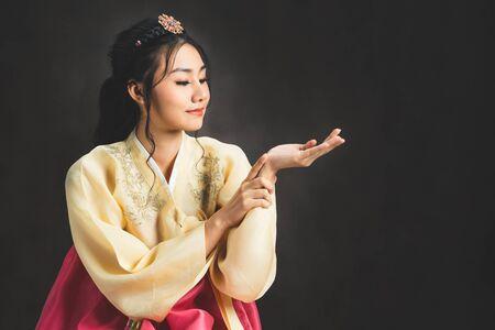 Korean woman wearing traditional korean dress (Hanbok) on black background in studio. Beautiful Korea culture.