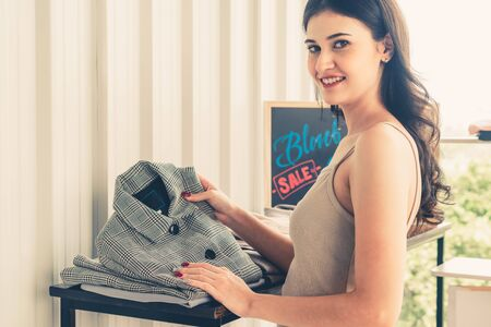 Beautiful woman shopping for clothes at retail apparel shop in the shopping mall. Modern trade lifestyle. Stockfoto