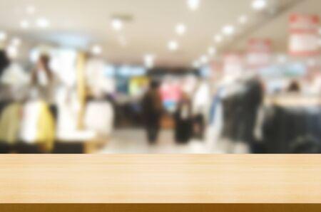 Holztisch im Einkaufszentrum oder Kaufhaus verwischt den Hintergrund mit leerem Kopienraum auf dem Tisch für die Produktpräsentation. Modernes Einkaufskonzept für Handel und Einzelhandel.