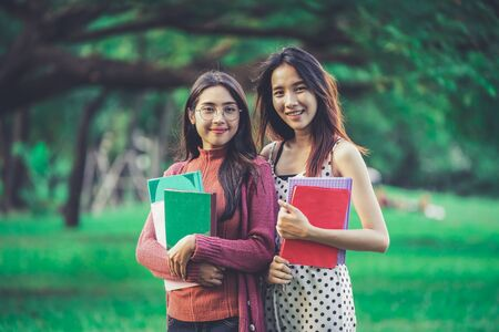Young woman students friends hold books in their hand while standing in college park. Education concept.