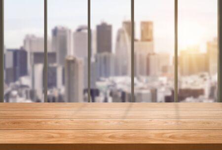 Tavolo in legno sullo sfondo dell'ufficio moderno del centro città con spazio vuoto per la copia sul tavolo per il modello di visualizzazione del prodotto. Interno della scrivania dell'area di lavoro e luogo per le attività aziendali.