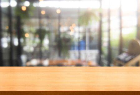 Holztisch im verschwommenen Hintergrund des modernen Restaurantraums oder Cafés mit leerem Kopienraum auf dem Tisch für Produktpräsentationsmodell. Designkonzept für die Restauranttheke im Inneren. Standard-Bild