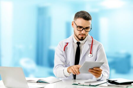 Doctor using tablet computer at the hospital. Medical healthcare and doctor staff service. Imagens
