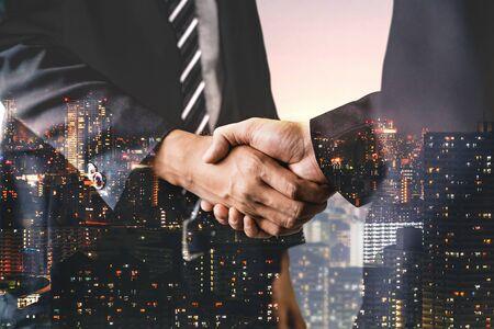 Doppelbelichtungsbild von Geschäftsleuten, die auf dem Bürogebäude der Stadt im Hintergrund den Erfolg der Partnerschaft zeigen. Konzept der Unternehmensteamarbeit, Vertrauenspartner und Arbeitsvereinbarung.