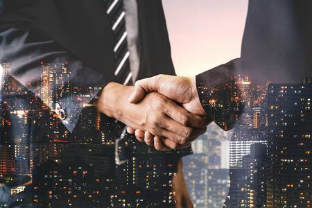 Immagine a doppia esposizione della stretta di mano degli uomini d'affari sull'edificio per uffici della città sullo sfondo che mostra il successo della partnership dell'affare d'affari. Concetto di lavoro di squadra aziendale, partner di fiducia e accordo di lavoro.
