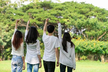 Young happy students of men and women raising hands celebrating and showing teamwork in the park of school or university. Charity, volunteer and unity concept.