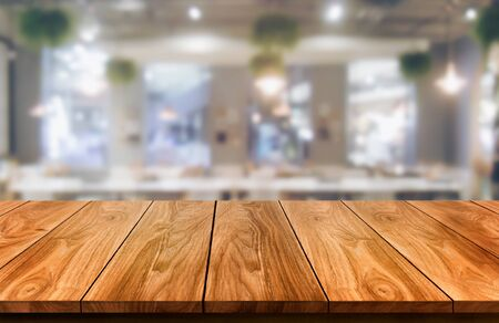 Wood table in blurry background of modern restaurant room or coffee shop with empty copy space on the table for product display mockup. Interior restaurant counter design concept. 版權商用圖片