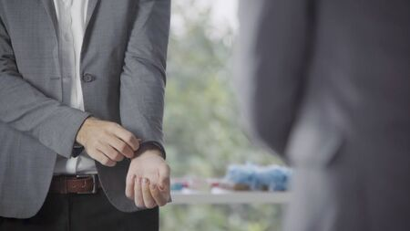 Man in formal business suit or groom costume getting dressed in dressing room preparing for working, engagement or wedding ceremony.