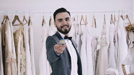 Groom giving the wedding diamond ring towards camera in wedding ceremony.