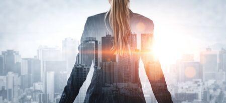 Doppelbelichtungsbild der Geschäftsperson auf modernem Stadthintergrund. Zukünftiges Geschäfts- und Kommunikationstechnologiekonzept. Surreales futuristisches Stadtbild und abstrakte Grafikschnittstelle mit Mehrfachbelichtung.