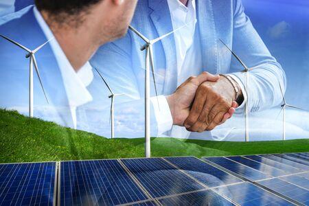 Doppelbelichtungsgrafik von Geschäftsleuten Handshake über Windturbinenpark und grüne erneuerbare Energiearbeiterschnittstelle. Konzept der Nachhaltigkeitsentwicklung durch alternative Energien.