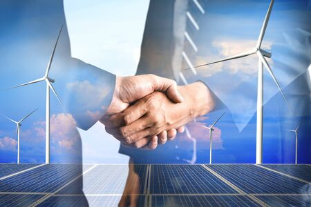Double exposure graphic of business people handshake over wind turbine farm and green renewable energy worker interface. Concept of sustainability development by alternative energy. 免版税图像