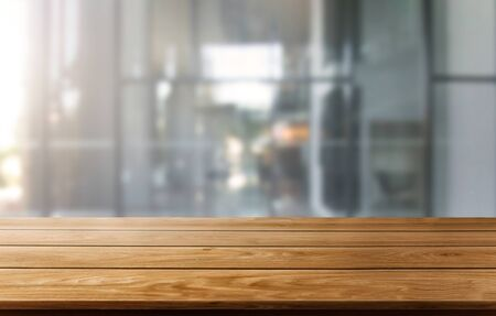 Wood table in city center modern office background with empty copy space on the table for product display mockup. Workspace desk interior and place for corporate business.