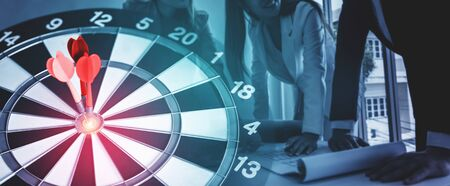 Business Target Goal For Success Strategy Concept - Red dart arrow hitting center goal on the dart board with business people working in background showing precision and success of business target. 写真素材 - 132021196