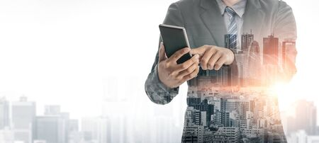 Double Exposure Image of Business Communication Network Technology Concept - Business people using smartphone or mobile phone device on modern cityscape background. Stock Photo